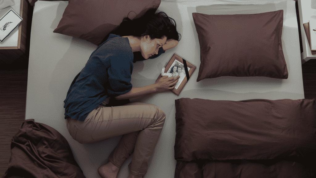 Mulher triste de luto deitada na cama segurando um porta retratos