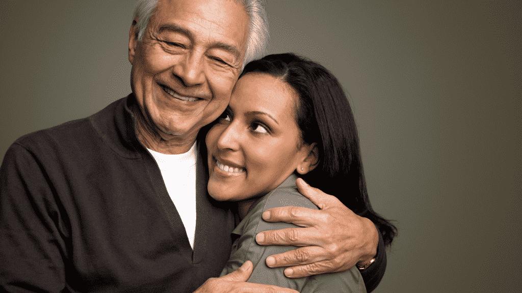 Pai e filha sorrindo e abraçados juntos