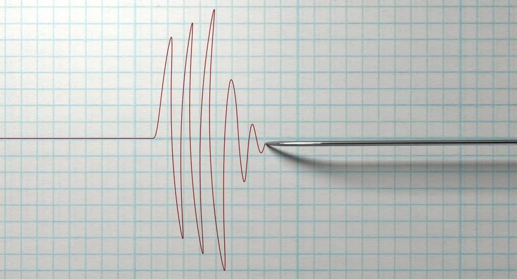 Close de um teste de detector de mentiras com polígrafo, desenhando uma linha vermelha em papel milimetrado em um fundo branco