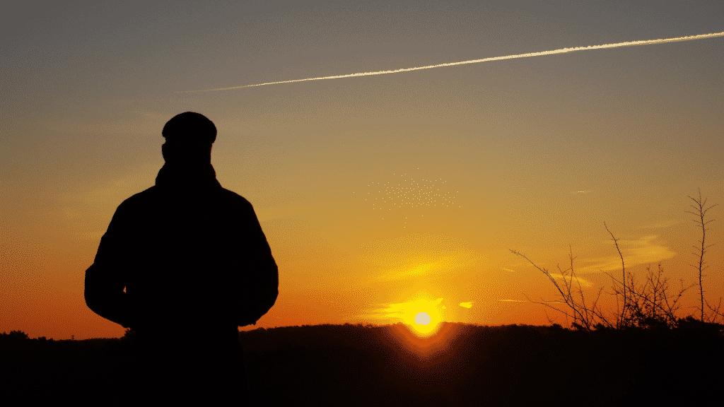 Homem observando o nascer do sol