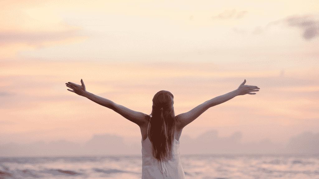 Mulher de braços abertos na praia observando o por do sol