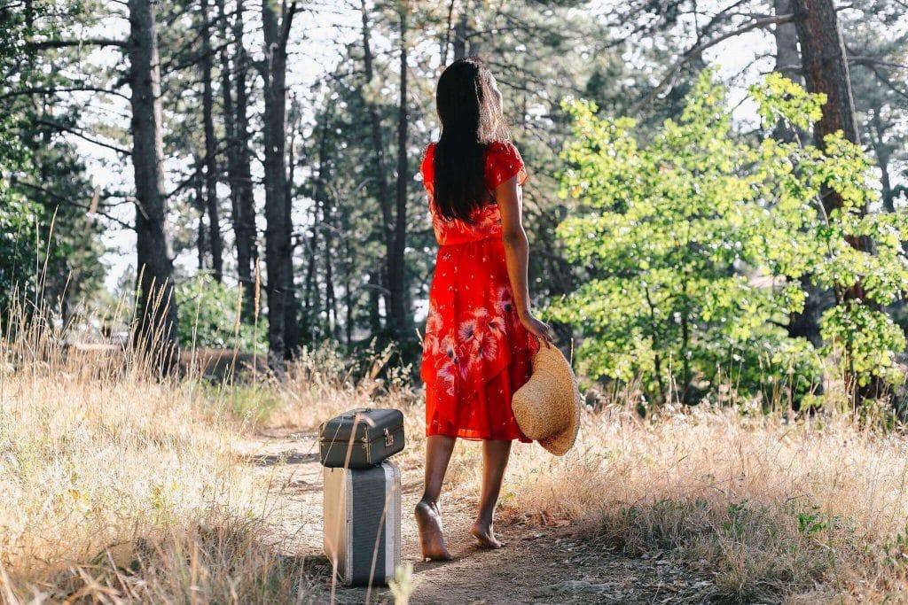Mulher branca segurando chapéu de palha numa floresta.