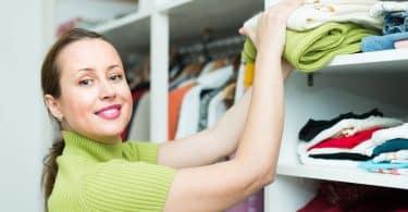 Mulher sorri e organiza roupas em armários.