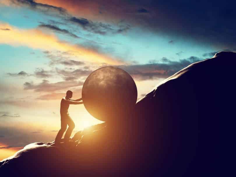 Homem segura uma bola de concreto gigante em morro.