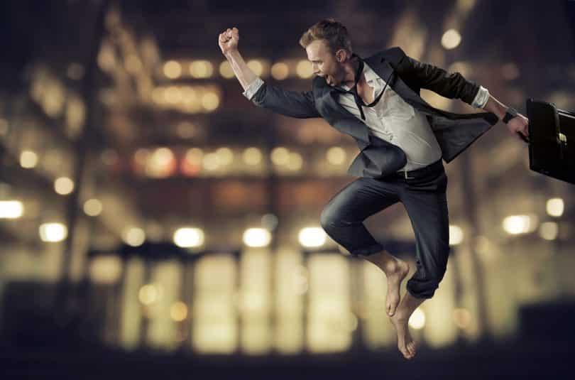 Homem salta no ar com a mão erguida.