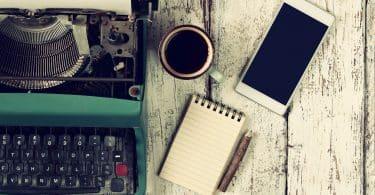 Máquina de escrever sobre superfície de madeira. Ao lado, há uma xícara de café, bloco de notas e celular.