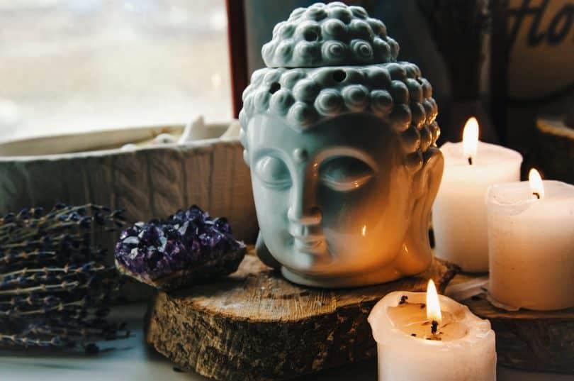 Cabeça de Buda, velas acesas e cristal roxo.