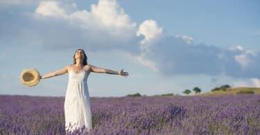Mulher com os braços abertos segura um chapéu em uma das mãos. Ela está em um campo de lavandas.