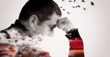 Homem apoia a cabeça sobre a mão. De sua cabeça, saem pássaros.