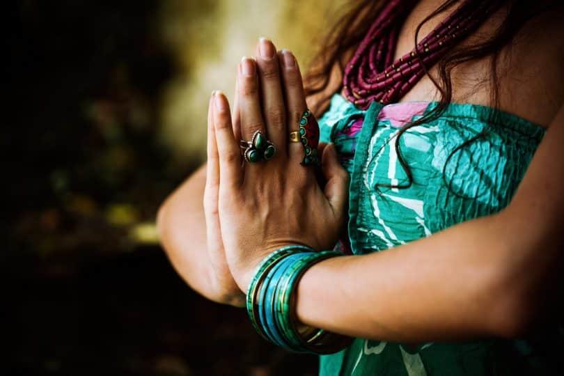 Mulher praticando o gesto do namaskara mudra.