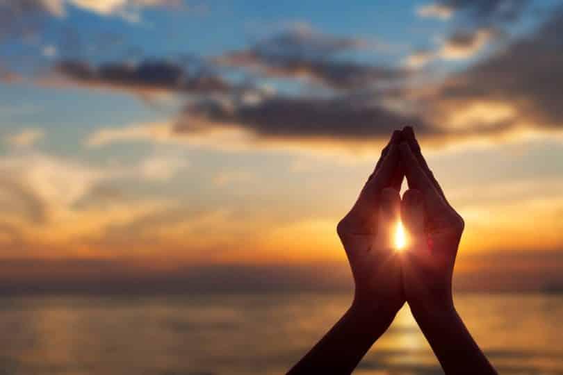Mãos juntas ao redor do Sol numa praia.