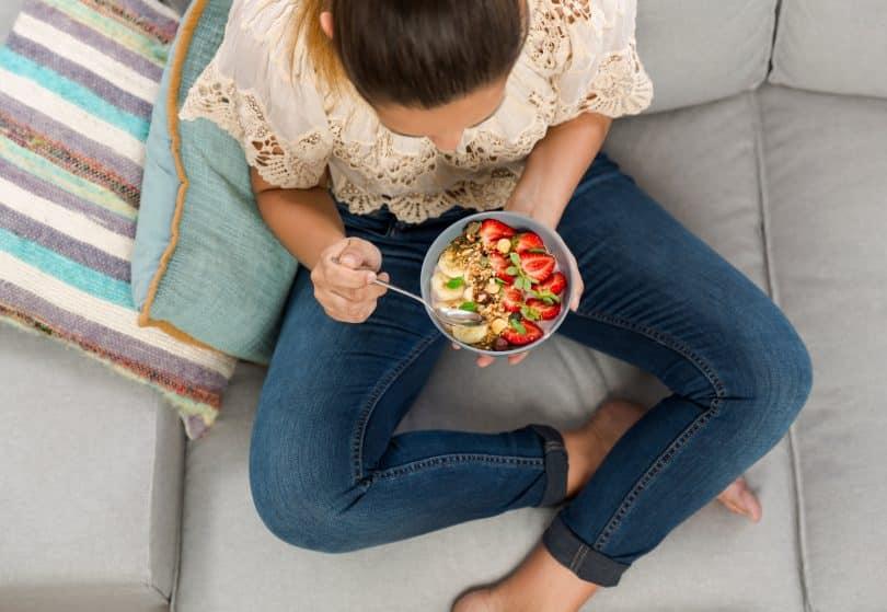Mulher comendo tigela de frutas.