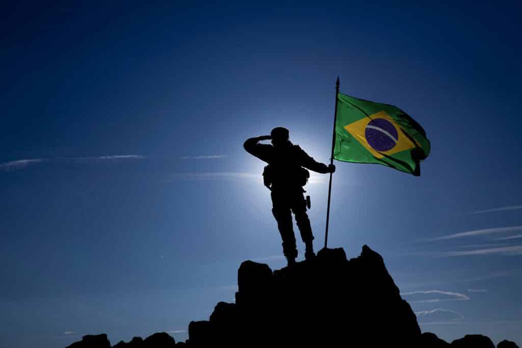 Soldado no alto da montanha com a bandeira brasileira