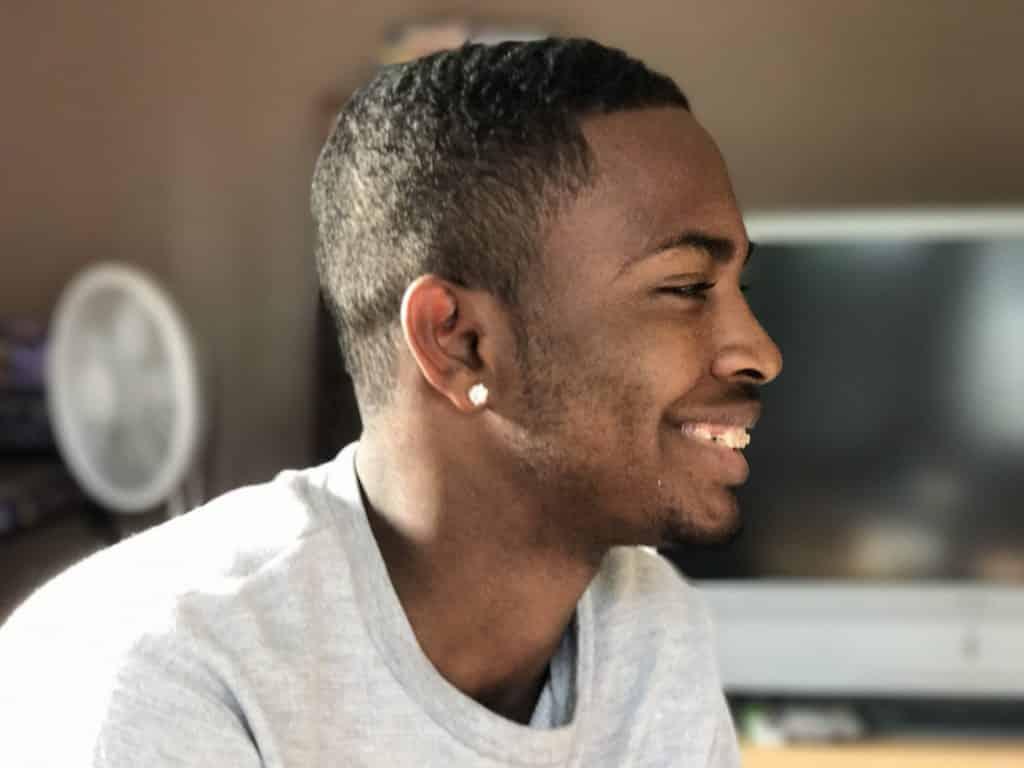 Perfil de homem negro sorrindo.