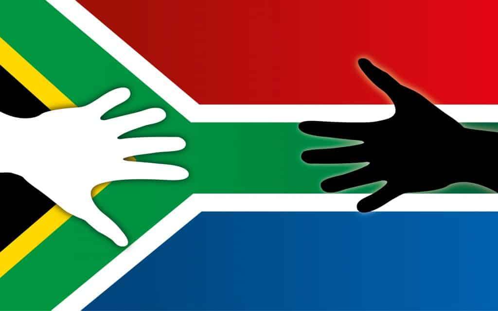 Bandeira da África do Sul com mãos coloridas e brancas pela paz.