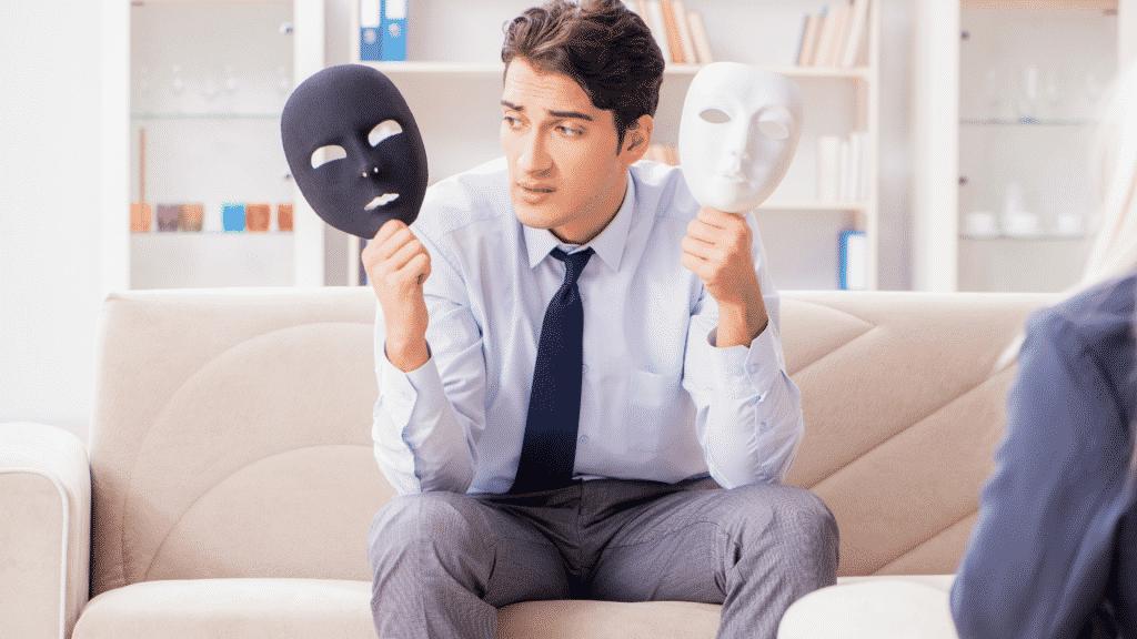 Homem sentado em dúvida, segurando duas máscaras: uma preta e uma branca.