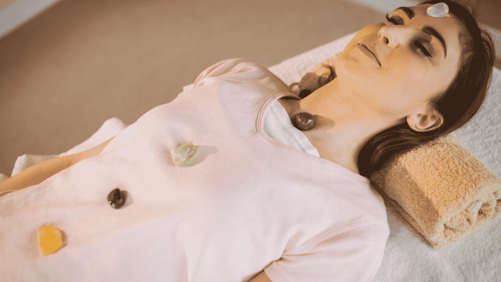 Mulher deitada com uma pedra em cada chakra do seu corpo