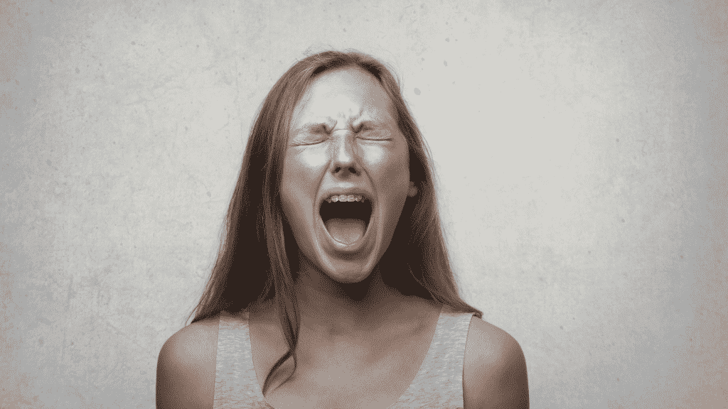 Mulher de olhos fechados, gritando e com expressão de raiva