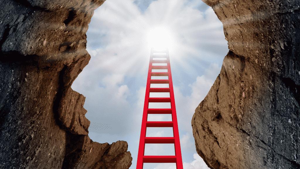 Silhueta de um rosto formado por pedras. Uma escada vermelha vai de encontro com o rosto, referindo-se à clareza mental.