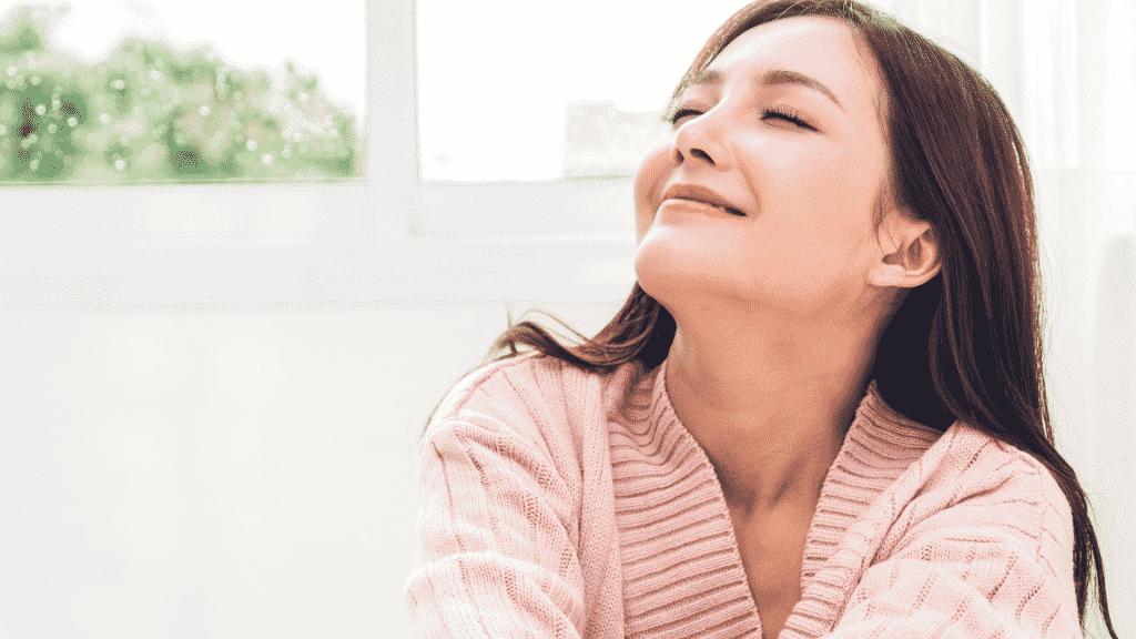 Mulher japonesa com os olhos fechados e sorrindo