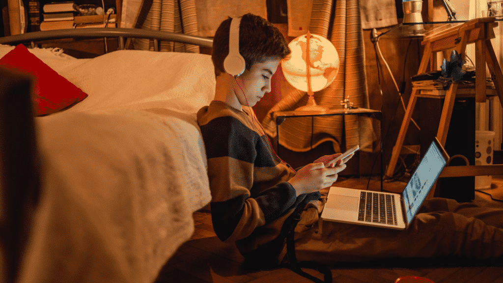 Adolescente sentado no quarto com fone de ouvido, celular e notebook