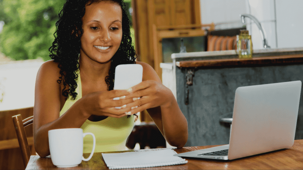 Mulher sorrindo enquanto manda mensagem pelo celular