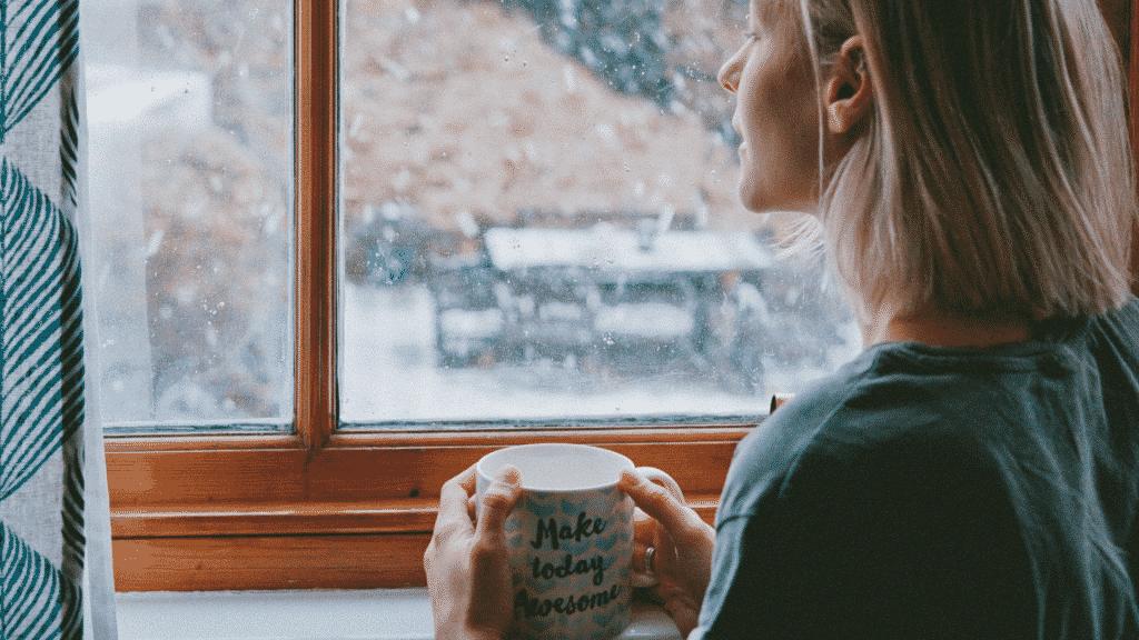 Mulher pensativa olhando pela janela enquanto segura xícara de chá