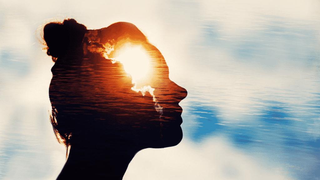 Silhueta de uma mulher e um céu aberto refletindo em sua mente