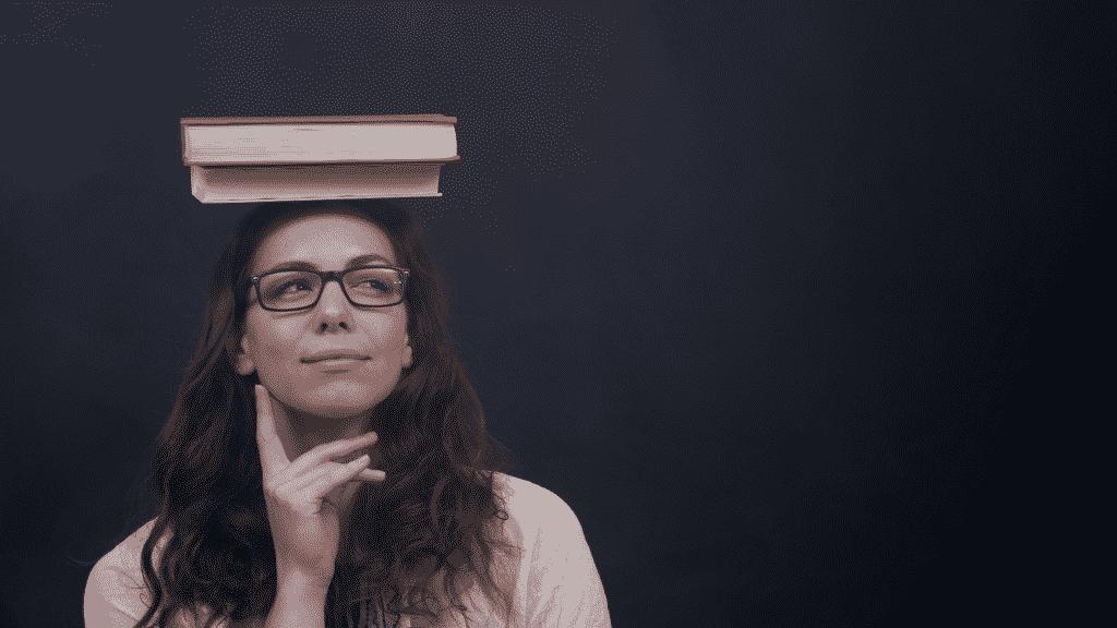 Mulher pensativa com dois livros equilibrados em cima da cabeça