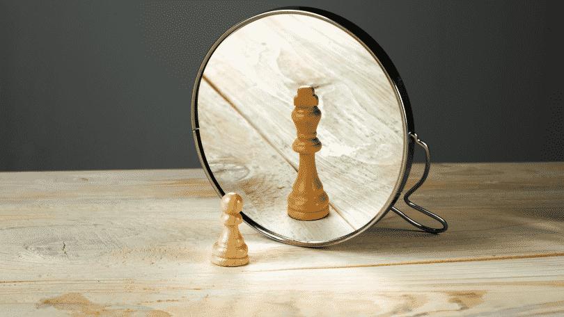 Peça de xadrez em frente ao espelho. Sua imagem refletida é bem maior