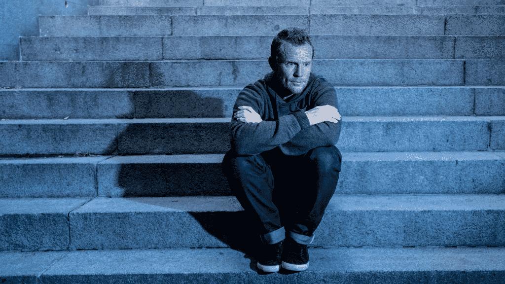 Homem sentado em uma escadaria, sozinho