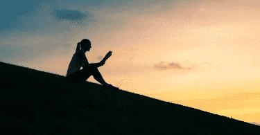 Mulher sentada em um gramado, lendo um livro