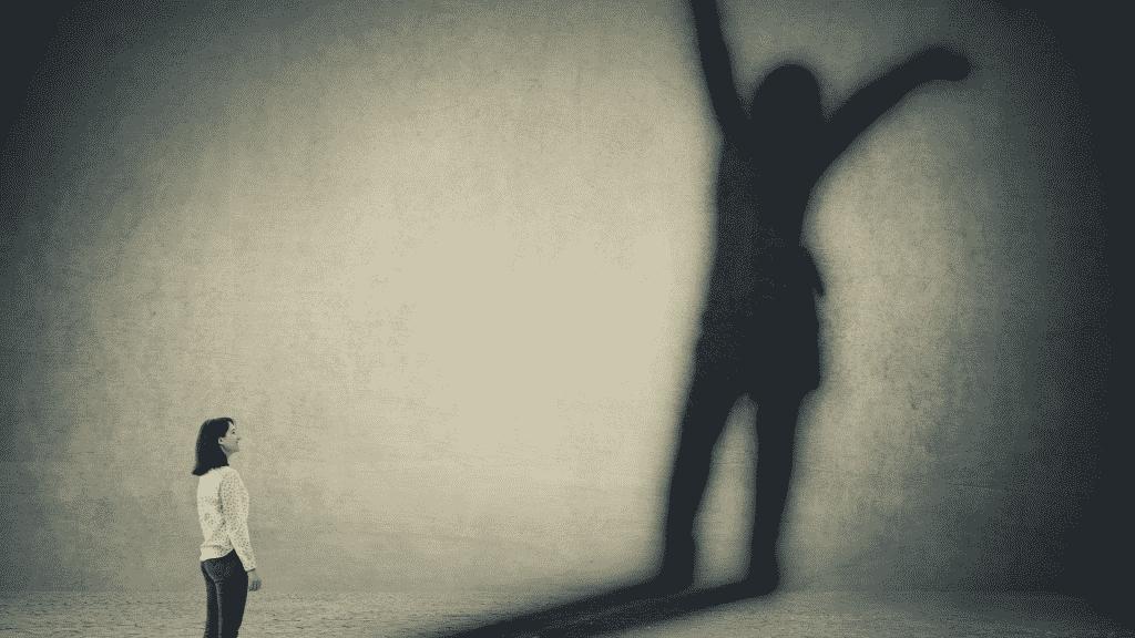 Mulher encarando sua sombra, que é bem maior que ela