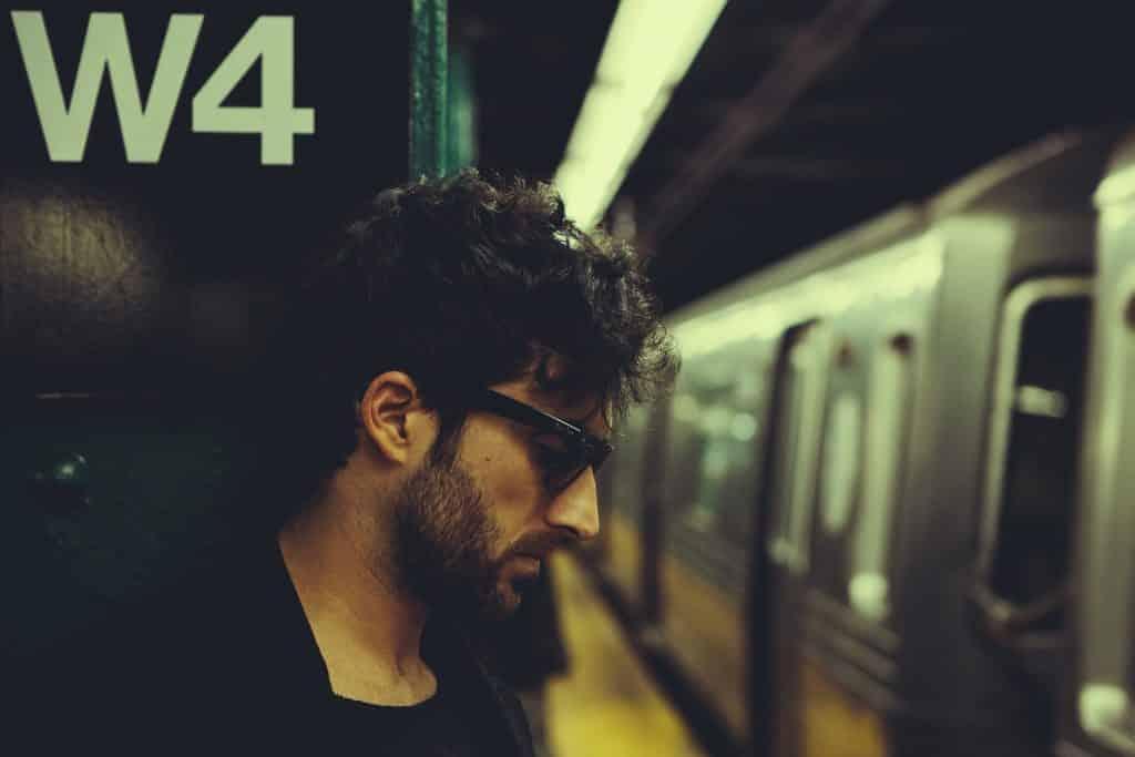 Homem branco numa estação de metrô.
