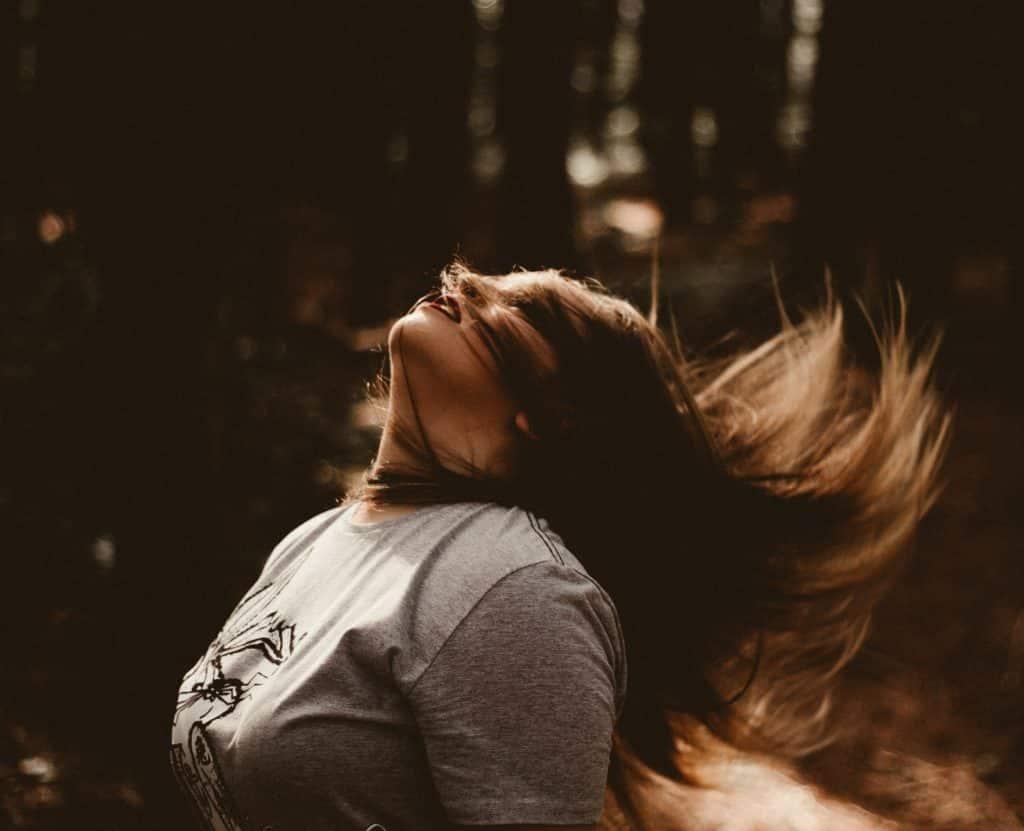 Mulher branca balançando os cabelos.
