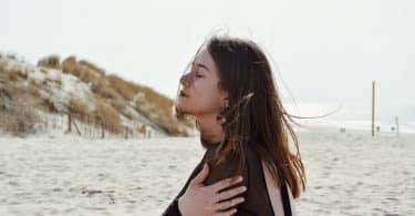 Mulher de olhos fechados numa praia.