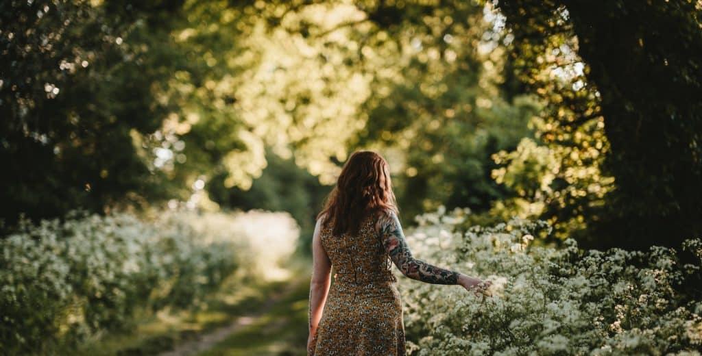 Mulher branca e ruiva de costas num jardim.