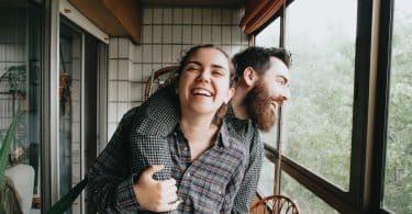 Homem e mulher brancos rindo abraçados.