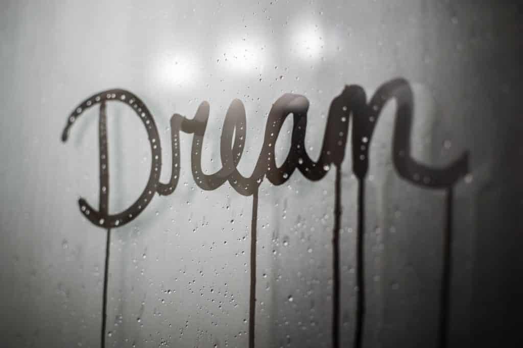 """Palavra """"dream"""" escrita num vidro embaçado."""