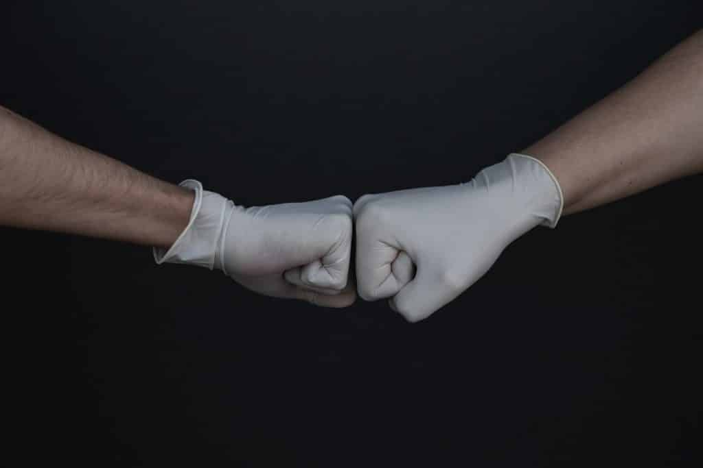 Mãos com luvas fechadas em punho.