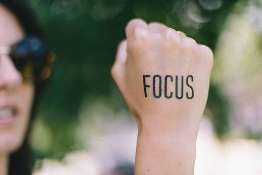 """Mão de mulher branca escrito """"focus""""."""