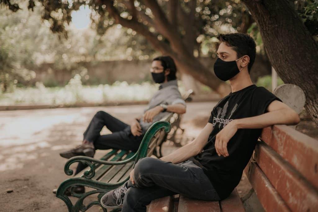 Homem usando máscaras sentados em bancos.