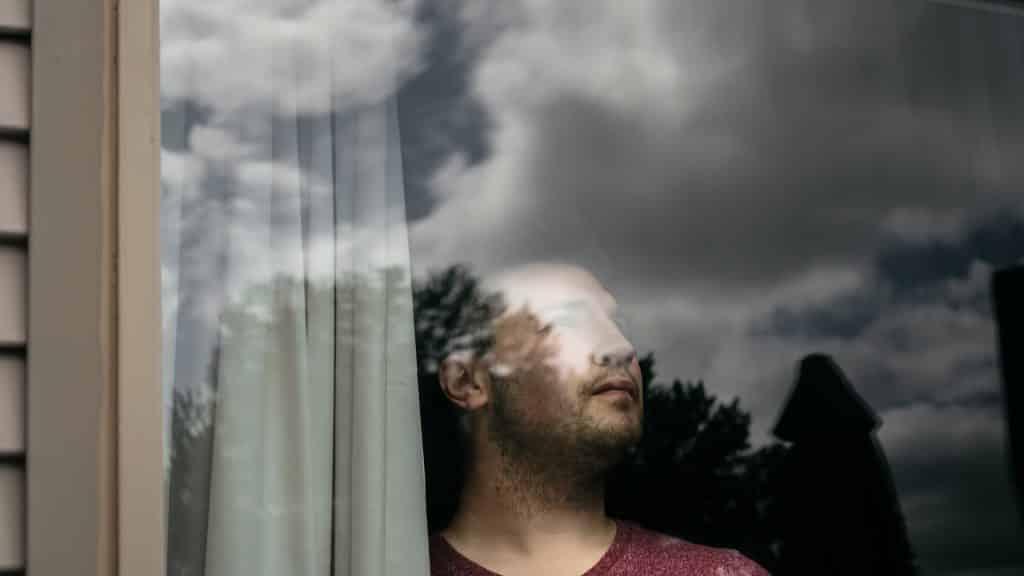 Homem branco olhando pro céu pela janela.