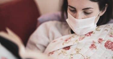 Mulher branca usando máscara enquanto lê livro.