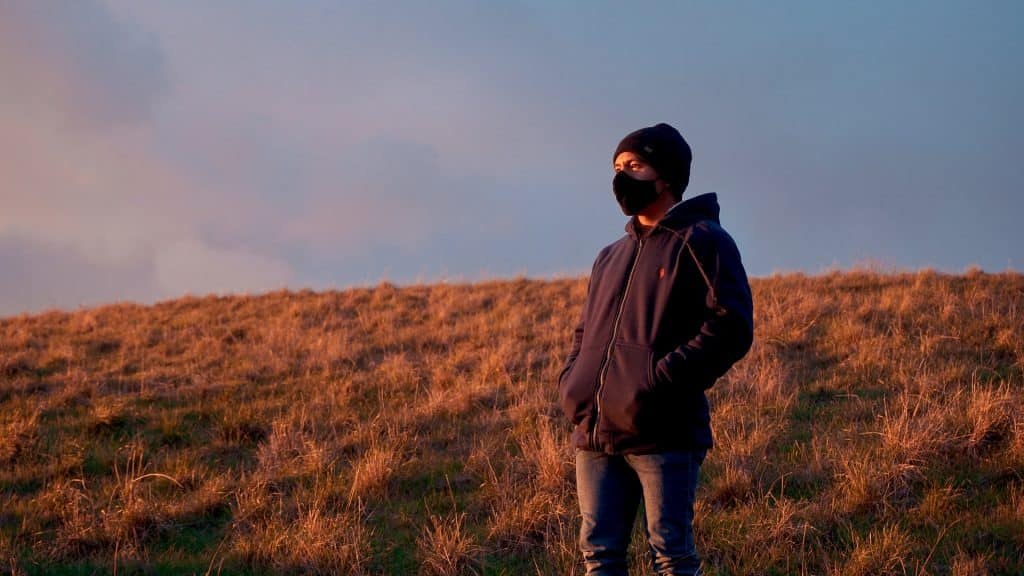 Homem branco com roupas de frio e máscara num campo.