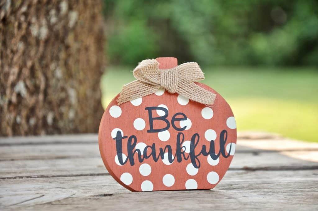 """Placa decorativa com a frase """"be thankful""""."""