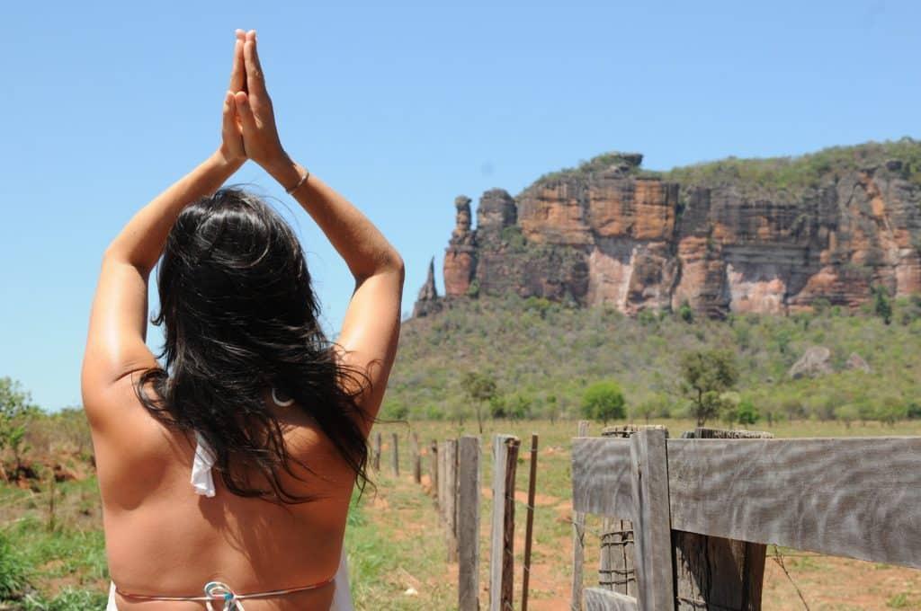 Mulher de costas em uma paisagem de montanhas.