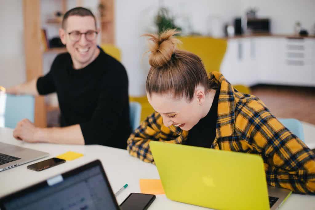Homem e mulher brancos rindo num escritório.