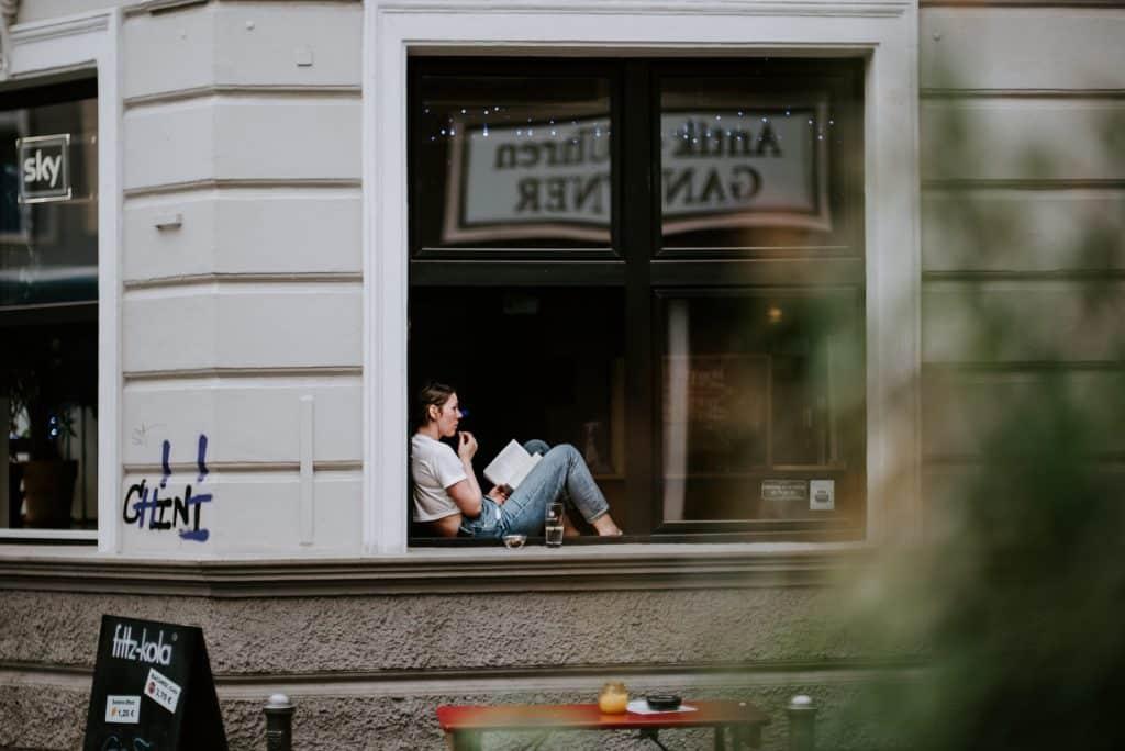 Mulher branca sentada numa janela lendo livro.