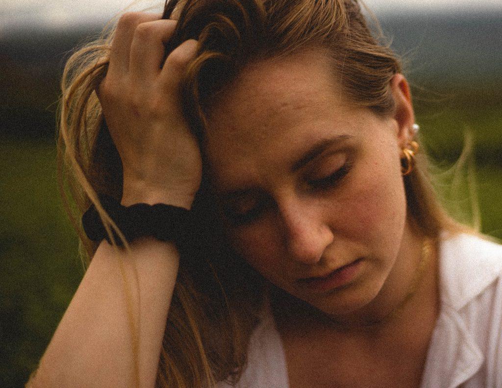 Mulher branca com a cabeça apoiada na mão.